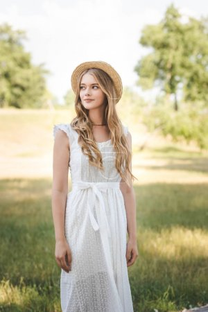 Photo for Beautiful girl with straw hat and white dress standing on meadow and looking away - Royalty Free Image