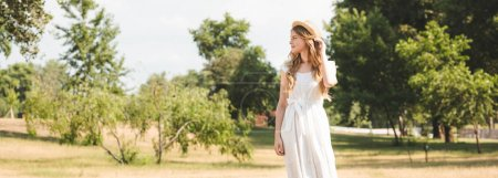Photo for Panoramic shot of beautiful girl with straw hat and white dress standing on meadow and looking away - Royalty Free Image