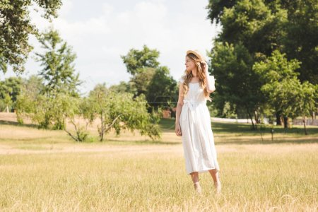 Photo for Beautiful girl in white dress and straw hat standing on meadow and looking away - Royalty Free Image