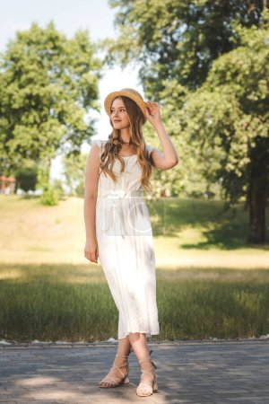 Photo for Full length view of beautiful girl in white dress and straw hat standing on meadow and looking away - Royalty Free Image