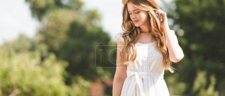 Photo pour Plan panoramique de belle fille en robe blanche touchant chapeau de paille et regardant vers le bas - image libre de droit