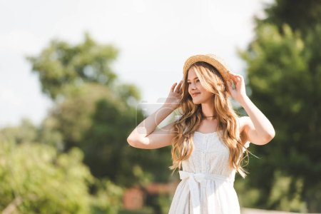Photo for Beautiful girl in white dress touching straw hat and smiling while standing on meadow and looking away - Royalty Free Image