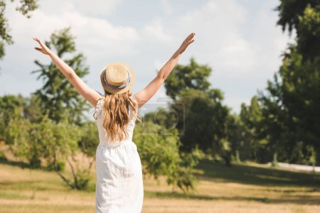 back view of girl in white dress and straw hat with hands in air