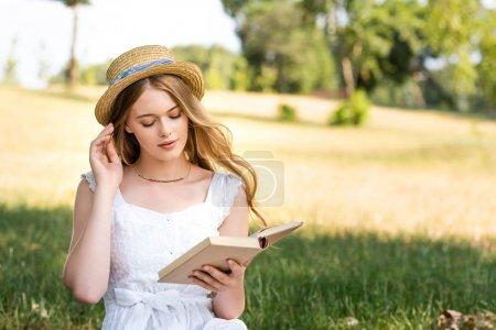 belle fille en robe blanche touchant chapeau de paille et livre de lecture tout en étant assis sur la prairie
