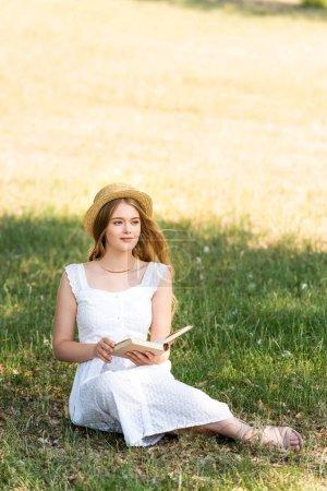 Photo pour Vue pleine longueur de belle fille en robe blanche et chapeau de paille tenant livre tout en étant assis sur la prairie et en regardant loin - image libre de droit