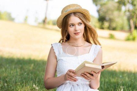Photo pour Belle fille en robe blanche et chapeau de paille tenant livre tout en étant assis sur la prairie et regardant loin - image libre de droit