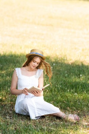 Photo for Full length view of beautiful girl in white dress and straw hat reading book while sitting on meadow - Royalty Free Image