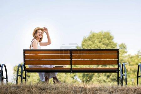 Photo pour Belle fille en robe blanche touchant chapeau de paille et souriant tout en étant assis sur le banc et en regardant la caméra - image libre de droit