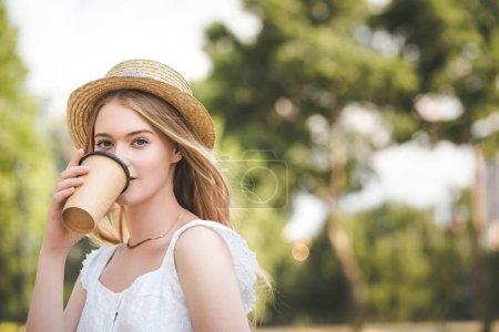 belle fille en robe blanche et chapeau de paille tenant tasse de café en papier et regardant la caméra