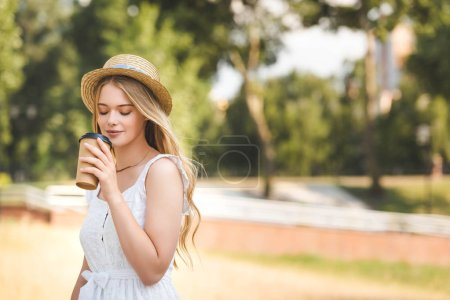 Photo for Beautiful girl in white dress and straw hat holding paper cup and drinking coffee with closed eyes - Royalty Free Image
