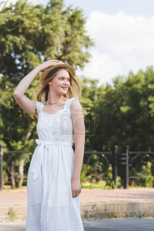 Photo for Beautiful young girl in white dress touching straw hat while smiling and looking away - Royalty Free Image