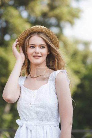 Photo pour Vue de face de belle jeune fille en robe blanche touchant chapeau de paille tout en souriant et en regardant loin - image libre de droit