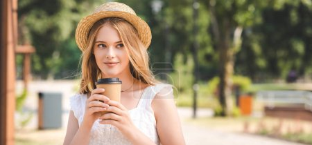Photo for Panoramic shot of beautiful girl in white dress and straw hat holding paper cup and looking away - Royalty Free Image