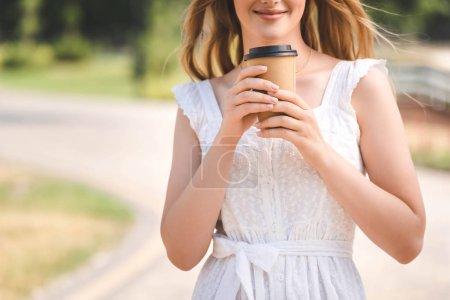 Ausgeschnittene Ansicht eines jungen Mädchens in weißem Kleid und Strohhut, das lächelt und eine Kaffeetasse aus Papier hält