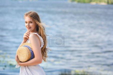 Photo pour Belle jeune fille debout sur le rivage de la rivière tout en tenant chapeau de paille et en regardant la caméra - image libre de droit