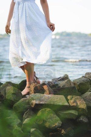 Photo pour Vue recadrée de fille dans la robe blanche marchant sur la rive rocheuse de fleuve - image libre de droit