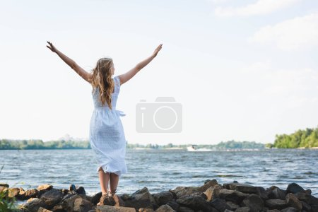 Photo for Full length view of girl in white dress standing on rocky river shore with hands in air - Royalty Free Image