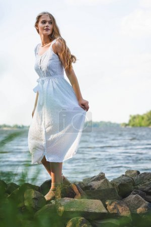 Photo for Selective focus of beautiful girl in white dress walking on rocky river shore and looking away - Royalty Free Image