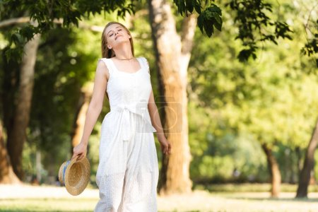 Photo for Beautiful girl in white dress holding straw hat while standing with closed eyes - Royalty Free Image