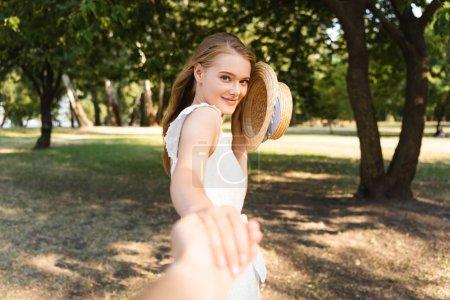 Photo pour Vue recadrée de l'homme tenant belle fille tandis que la jeune femme tenant chapeau de paille et regardant la caméra - image libre de droit