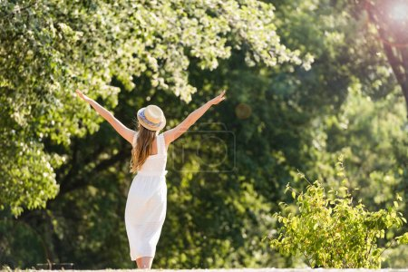 back view of girl in white dress walking in park with hands in air