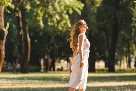 Photo pour Vue latérale de belle fille en robe blanche tenant chapeau de paille tout en souriant et debout sur la prairie avec les yeux fermés - image libre de droit
