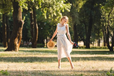Photo for Full length view of beautiful girl in white dress holding straw hat while smiling and standing on meadow with closed eyes - Royalty Free Image