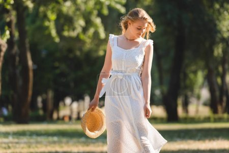 beautiful girl in white dress holding straw hat while smiling and standing on meadow and looking down