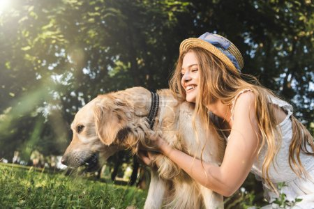 Photo for Beautiful young girl in white dress and straw hat hugging golden retriever while smiling, sitting on meadow and looking at dog - Royalty Free Image