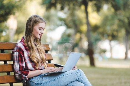 Photo pour Foyer sélectif de belle fille en vêtements décontractés assis sur un banc en bois dans le parc et en utilisant un ordinateur portable - image libre de droit