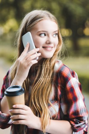 Photo for Portrait shot of beautiful girl in casual clothes holding paper coffee cup and smiling while talking on smartphone and looking away - Royalty Free Image