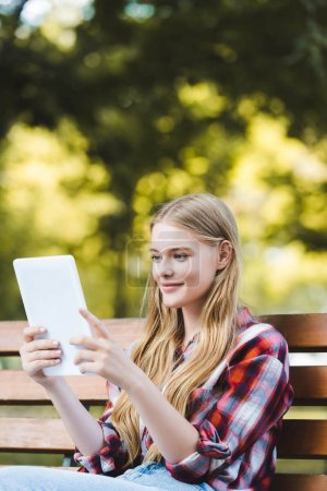 Photo for Selective focus of beautiful young girl in casual clothes sitting on wooden bench in park and using digital tablet - Royalty Free Image