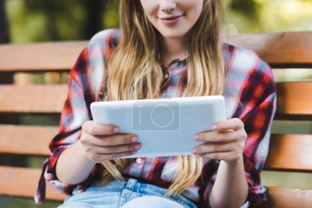 cropped view of young girl in casual clothes sitting on wooden bench in park and using digital tablet