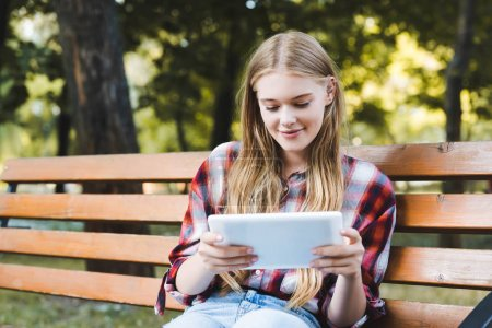 Photo for Young girl in casual clothes sitting on wooden bench in park and using digital tablet - Royalty Free Image