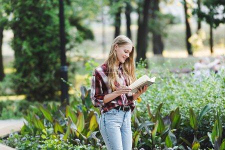Photo pour Belle fille en vêtements décontractés souriant tout en lisant le livre - image libre de droit