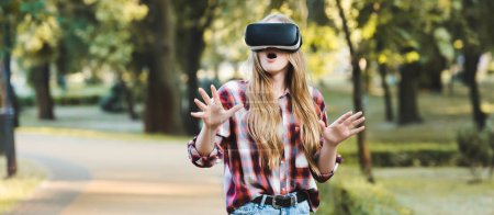 Photo for Panoramic shot of surprised young girl in casual clothes using vr headset - Royalty Free Image