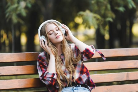 Beautiful girl in casual clothes listening to musi...