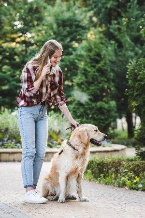 Photo pour Vue pleine longueur de belle jeune fille en vêtements décontractés se réveiller dans le parc avec golden retriever et parler sur smartphone - image libre de droit