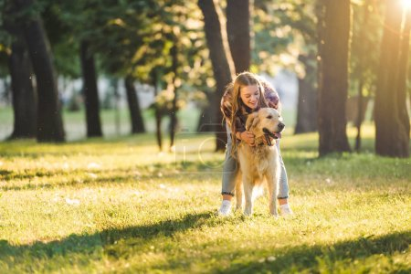 full length view of beautiful girl in casual clothes hugging golden retriever while standing on meadow in sunlight