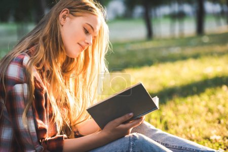 Photo for Side view of beautiful girl in casual clothes sitting on meadow in sunlight and reading book - Royalty Free Image
