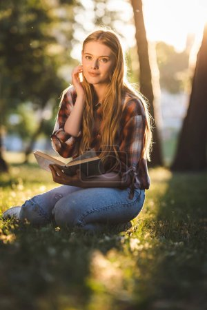 full length view of beautiful girl in casual clothes sitting on meadow in sunlight, holding book and looking at camera