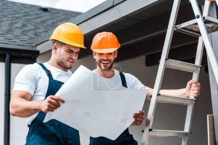 cheerful builders in helmets looking at paper near ladder