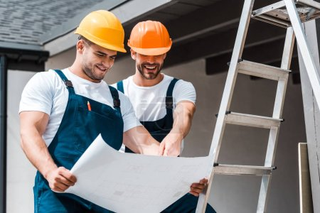 Photo for Happy architects in helmets looking at paper and smiling near ladder - Royalty Free Image
