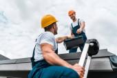 """Постер, картина, фотообои """"low angle view of handyman in helmet giving toolbox to happy colleague """""""