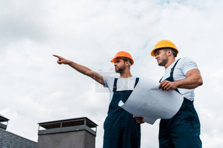 Photo for Low angle view of handsome architect pointing with finger near coworker in helmet holding paper - Royalty Free Image