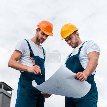 Photo pour Vue à faible angle de beaux constructeurs en uniforme en regardant le papier avec le plan - image libre de droit