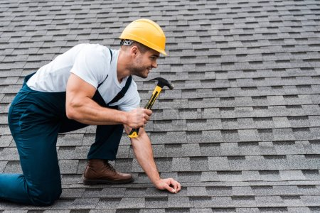 Photo for Handsome repairman in helmet holding hammer while repairing roof in house - Royalty Free Image