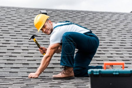 Photo for Selective focus of handsome handyman repairing roof - Royalty Free Image