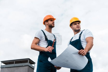 Photo for Low angle view of architects in helmets against sky with clouds - Royalty Free Image