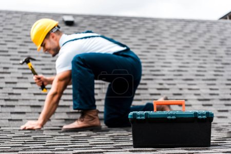 Photo for Selective focus of toolbox near repairman holding hammer on rooftop - Royalty Free Image